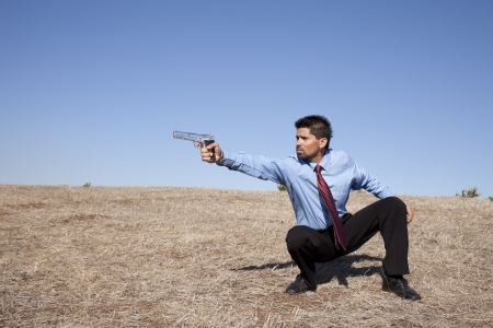 Powerful businessman with a gun in outdoor Stock Photo - 16389178