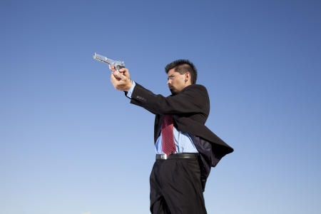 Powerful businessman with a gun in outdoor Stock Photo - 16387211