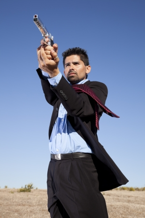 Powerful businessman with a gun in outdoor Stock Photo - 16387491
