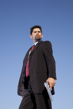Powerful businessman with a gun in outdoor Stock Photo - 16387429