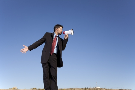 communicate concept: Businessman speaking with a megaphone with the blue sky as background (wide format photo) Stock Photo