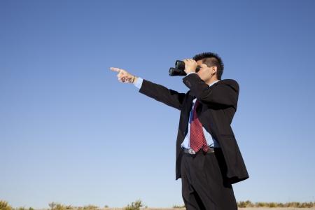 Businessman in outdoor looking though binoculars Stock Photo - 16387205