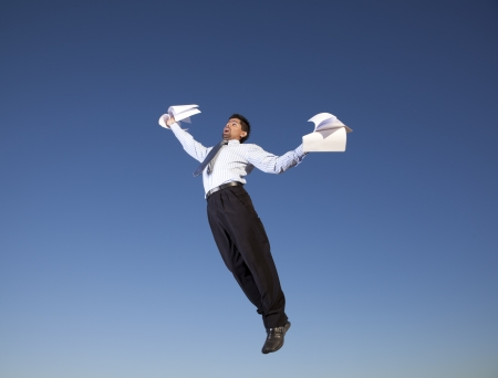 throw away: Businessman jumping in the air holding document papers in his hands