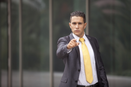 Businessman next to his office pointing to you photo