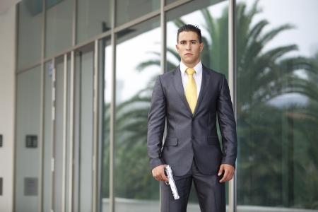 violence in the workplace: Hombre de negocios de seguridad de gran alcance que apunta un arma Foto de archivo