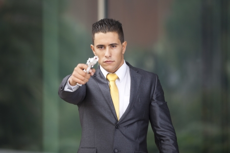 violence in the workplace: Powerful security businessman aiming a gun
