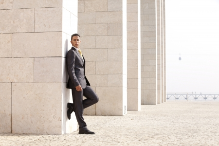 confident businessman next to some wall looking down photo