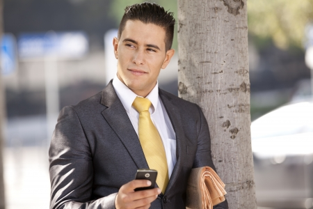 Businessman relaxing next to a tree at the city park, sending short messages over his cellphone photo