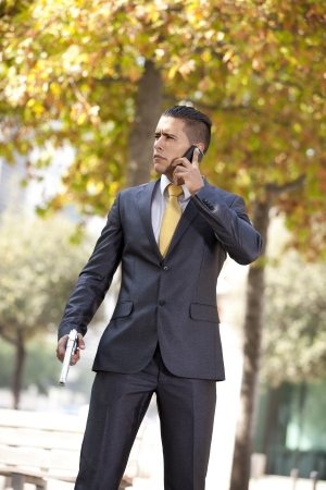 Powerful security businessman talking at his cellphone with a handgun in his belt photo