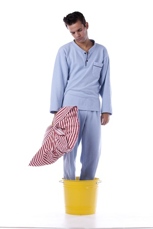 sleepwalker: Young man dress with nightclothes inside a yellow bucket (isolated on white)