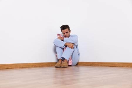 Young man with nightclothes sit at the room corner with fear Stock Photo - 16387250