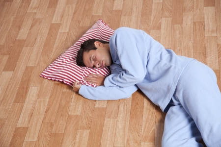 nightclothes: Young man dress with nightclothes sleeping on the floor (isolated on white)