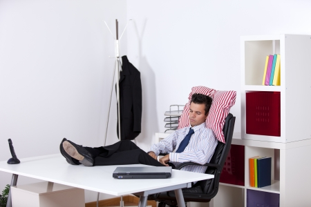 Businessman sleeping at his office with his shoes on the table photo