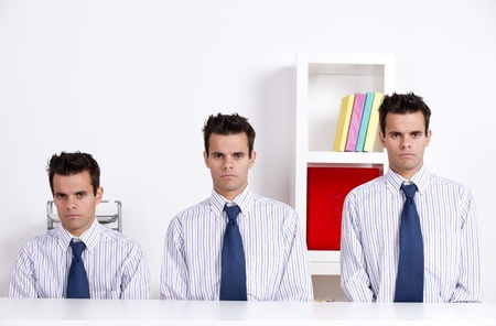 clone: Three businessman with diferent sizes at the office desk