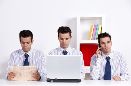 clone: Three twin businessman working at the office, reading the newspaper, on the phone and working with the laptop