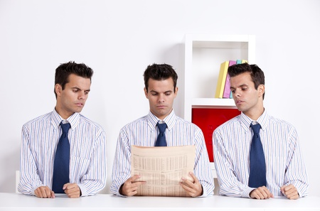 Three businessman at the office peeking and reading a newspaper Stock Photo - 16388873