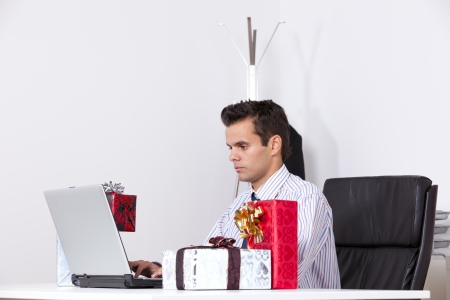 Businessman at his office working with his laptop with presents on the table Stock Photo - 16387443