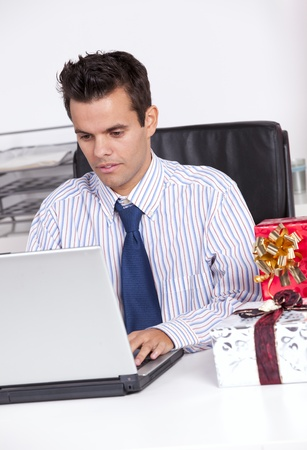 Businessman at his office working with his laptop with presents on the table Stock Photo - 16388608
