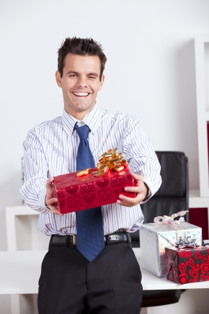 Happy businessman at his office giving valentine day gifts photo