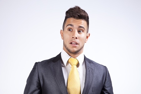 Young businessman with a fear expression on his face (isolated on gray) Stock Photo - 16388882