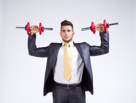 Strong businessman lifting heavy weights