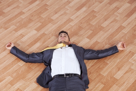 unconscious: young businessman fainted on the office floor