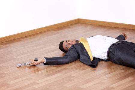 Businessman lying dead in the office floor with a gun in his hand photo
