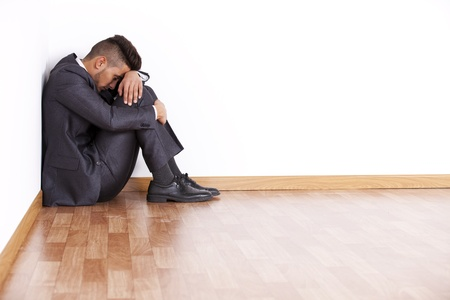 worry: Businessman at the corner of his office room with fear  Stock Photo