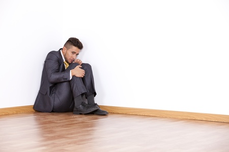 down sitting: Businessman at the corner of his office room with fear  Stock Photo
