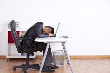 perezoso: Hombre de negocios cansado a dormir en su computadora port�til en la oficina Foto de archivo