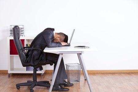 Tired businessman sleeping over his laptop at the office