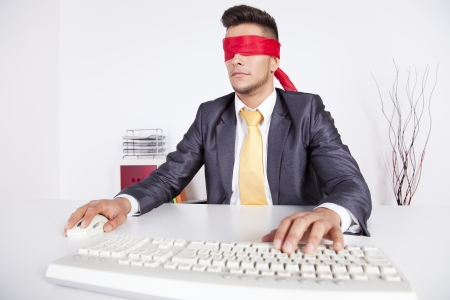 Businessman at his office with scarf covering his eyes while working with his computer Stock Photo - 16387564