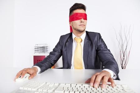 ojos vendados: Hombre de negocios en su oficina con el pañuelo que cubre sus ojos mientras trabaja con su ordenador
