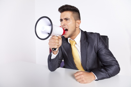 assertive: Handsome businessman at his office screaming over the megaphone