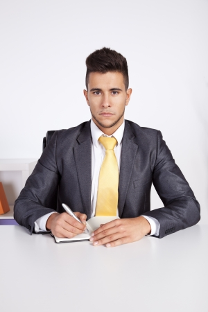 Businessman at his office taking some notes in his agenda photo