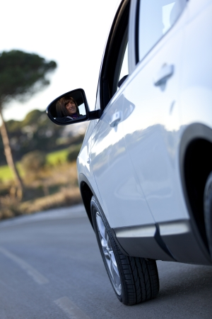 Beautiful woman face reflected on the side mirror of her new car Stock Photo - 16479745