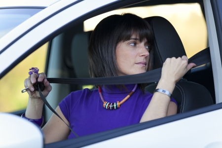 Woman inside the car putting her safety belt photo