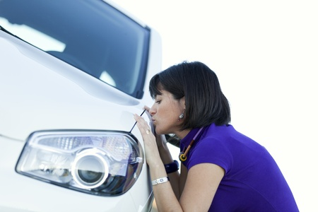 Beautiful woman kissing her new car