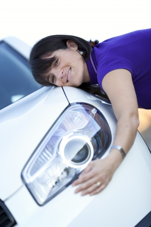 Beautiful woman embracing her new car photo