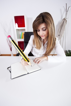 Businesswoman taking some notes on her notepad with a giant pencil photo