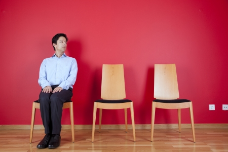Businessman sited next to a red wall Stock Photo - 16389196