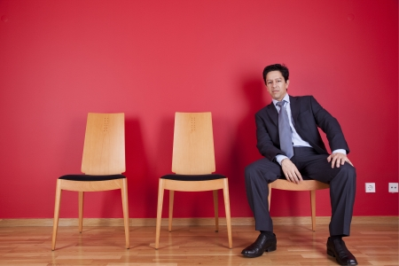 Businessman sited next to a red wall Stock Photo - 16389272