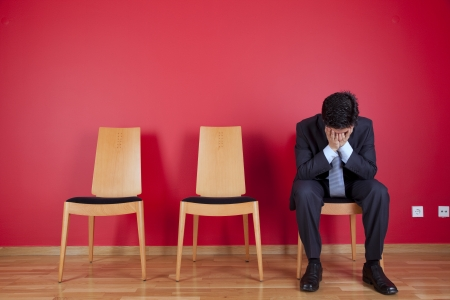 Sad businessman sited next to a red wall Stock Photo - 16389193