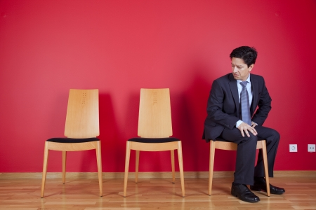 Jealous businessman looking to empty chairs Stock Photo - 16389202