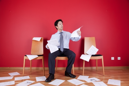 Businessman reading a document in a messy office full of papers on the floor photo