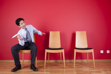 businessman sited next to a red wall trowing paper planes Stock Photo - 16389142
