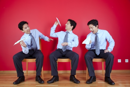 Three twin businessman sited next to a red wall trowing paper planesl Standard-Bild