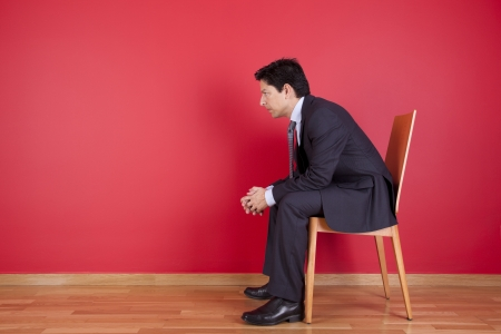 Businessman sited next to a red wall Stock Photo - 16389201