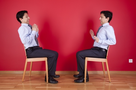 Confrontation between two twin businessman sited next to a red wall Stock Photo - 16389180