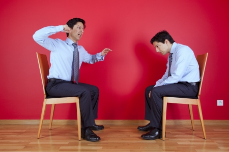 Conflict between two twin businessman sited next to a red wall Stock Photo - 16389195